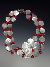 """Perfect for a festive occasion! A 2"""" x 2"""" carved black (only one left) or white mother of-pearl flower rests on 2 strands of iridescent gray-black mother-of-pearl ovals highlighted with tiny red coral florets. 20"""""""