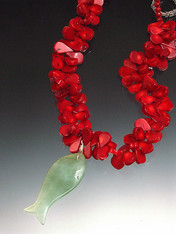 "Hand-carved green jade fish floats gracefully on a 19"" strand of red coral florets."