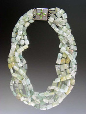 An opulent statement torsade featuring 5 strands of Grade AAA faceted aquamarine rectangles in delicate tones of pale aqua, cloud, and light green blend into a stunning collar with maximum impact. Hand-knotted with aqua silk. A custom clasp of marquis shaped peridot stones set in sterling silver can be worn as a center or side highlight for added impact. 20""
