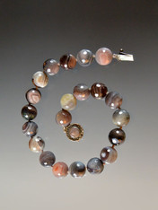 This striking necklace features brilliant 16mm faceted Botswana Agate beads with flashes of gray, pink, pale brown, ivory and other subtle tones with double Japanese hand-knotted silk.  19""