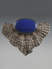 "This dramatic pin is from the 1930s.  It features a large cobalt cabochon set in a beautifully detailed marcasite fan shape and sterling silver.  3"" x 2"""