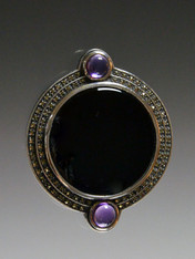 This vintage circular pin features highly reflective onyx with a carved marcasite frame.
