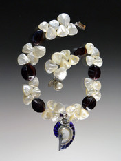 """This dramatic limited-edition necklace features huge grade AAA mother-of-pearl fans, violet oyster 4-sided shells, and a one of a kind natural Indonesian sterling purple and white nautilus shell with a sterling freshwater pearl clasp. Necklace 18"""" Nautilus shell 3"""""""