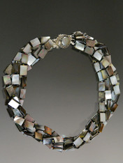 """This fabulous multi strand torsade of faceted mother-of-pearl tiles spaced with tiny jet Swarovski crystals shoots of sparks of black, white, bronze, and many other tones, held with a custom sterling silver mabe pearl clasp. Wear it for any occasion - understated yet super elegant. 20"""""""