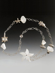 """This one of a kind sterling silver chain necklace features mother-of-pearl faceted slices and sterling silver starfish, seashells, and other marine creatures collected over many years.  28"""""""