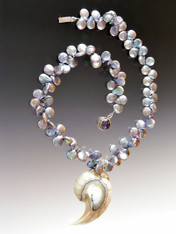 """This delightful necklace features peacock silver top drilled petal shaped pearls with an unusual blue centered, spherical white one-of-a-kind Nautilus Shell Pendant. 18"""""""