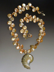 "A luminous natural outlined nautilus shell anchors a strand of grade AAA champagne peach coin pearls.  Absolutely stunning.  18""  Nautilus Shell 2"""
