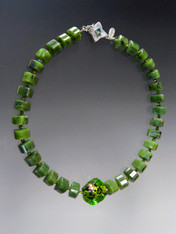 "Green is one of the hottest trends in jewelry this year.  This magnificent statement necklace features grade AAA green jade faceted thick wheels with a fabulous large limited edition Venetian glass dichoric glass sasso* three dimensional center bead and a sterling apatite clasp.  20""  ONLY TWO!"