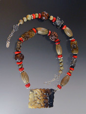 This piece is a real showstopper with a global vibe. The components are special pieces I've collected over the years. The highlight is a gorgeous piece of hand-carved multi-toned brown jade suspended from a strand of carved jade, red coral, Bali sterling silver, and Brazilian carved wood.  24""