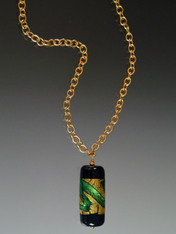 "This dramatic Venetian glass pendant suspended from a 24K Russian gold plated chain reminds me of a large battery-it is coated with 24K gold foil and bright green swirls. Toss it on and go. 24""."