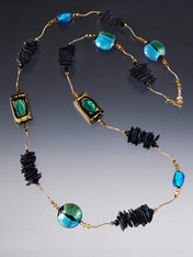 """A statement rope with gold that glitters and brilliant jewel tones right for now!      Clusters of black biwa pearls     14K curved tubes     24K Swarovski crystals     Custom designed and imported from Italy 24K gold and silver foil Venetian glass in aqua, gold, green and black      Tiny clasp that gives you the option of wearing this 35"""" rope double or single     Create a special look day or night"""
