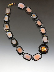 "This very popular design is features subtle burnt orange agate rectangles with natural black trim spaced with jet Swarovski crystals feature a matte onyx donut centered with a 24K gold topaz Venetian glass disc.  Onyx sterling clasp 19"" Choose rectangles or ovall beads."