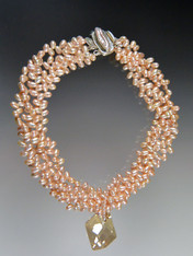 """This bold statement collar features multi strands of tiny freeform petal pink freshwater pearls, a """"cosmic"""" Swarovski crystal pendant and a mabe pearl sterling clasp."""