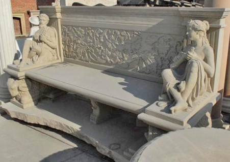 "HAND CARVED SANDSTONE BENCH FEATURES MALE AND FEMALE AT ARMS, RAMS AS LEGS, 98"" WIDE,"