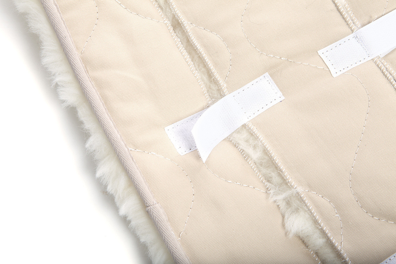 Hook and loop fasteners on back of sheepskin stroller liner for easy installation and removal.