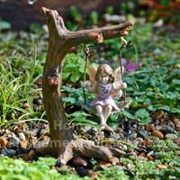 Tiny fairy on a tree swing