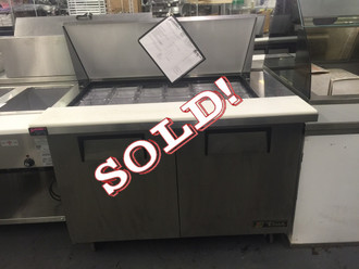 "USED True Mega Top Sandwich/Salad Unit, (18) 1/6 size (4""D) poly pans, stainless steel insulated cover, 8-7/8""D cutting board, stainless steel top, front, sides, aluminum back, (2) full doors, (4) PVC coated wire shelves, white aluminum interior with stainless steel floor, 5"" castors, 1/3 HP, 115v/60/1, 8.6 amps, 7' cord, NEMA 5-15P, cULus, NSF, CE, MADE IN USA."
