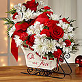 """A modern, fresh take on the traditional sleigh arrangement, we bring together red roses, red carnations, and red mini carnations, offset by snowy white Peruvian lilies and chrysanthemums, accented with an assortment of Christmas greens. Presented in a white holiday sleigh, that reads, """"Oh, what fun!"""" on the side in a scrolling red font"""