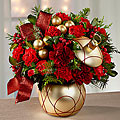 Rich red roses capture your attention with their swirling array of petals surrounded by burgundy carnations and mini carnations and accented with holly, lush Christmas greens, shining matte gold glass balls, and burgundy ribbon. Presented in a keepsake matte gold ceramic rounded vase, with a lid, to mimic the look of a Christmas ornament,