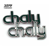 Dark green plastic Chaly frame badges with a chrome finish...
