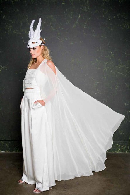 Add the Valentim cape to any House of Ollichon piece to create a striking, modern spin on the traditional veil. This stunning draped cape is made from silk chiffon providing an illusion over layer. You can wear the Valentim in three ways; cold-shoulder,Sherlock cape, or slung around the elbows.