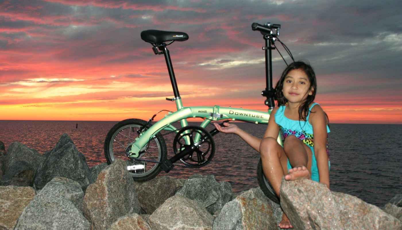 mini folding bike during sunset with little girl