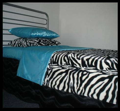 Zebra Bedding set shown with light turquoise satin sheets and jet black bed skirt