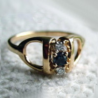 14k gold stirrup ring with diamonds and sapphire.