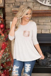 White long-sleeved babydoll top with a gold pocket