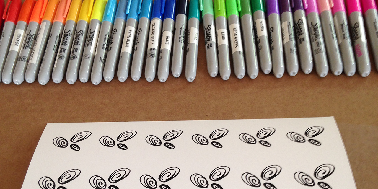 Shows about 30 Sharpie colors laid out in a row with a Color Tester for Creative Progress Maps on a museum-quality print