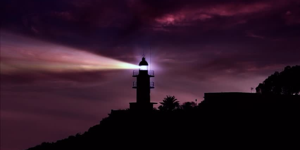 A lighthouse beaming light at night