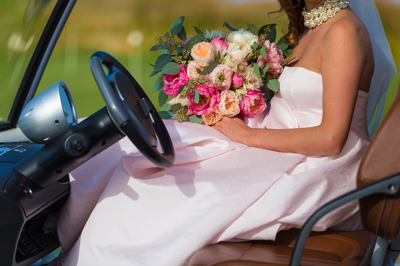 Bride with flowers in golf cart