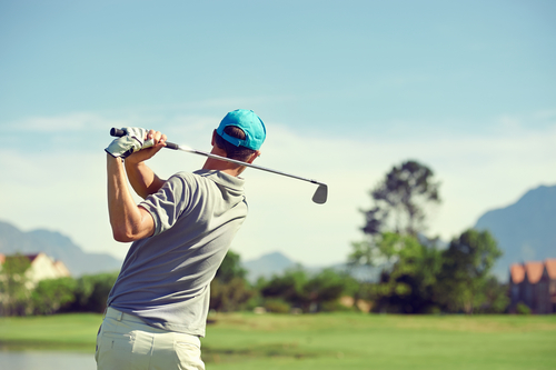 Golfer-hitting-golf-shot-with-club-on-course-while-on-summer-vacation