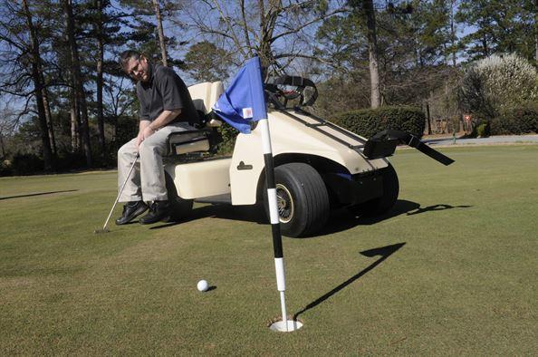 man-putting-while-sitting-on-golf-cart