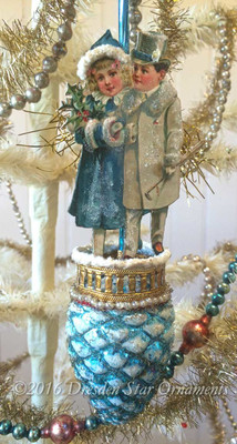 Wintery Boy an Girl on Light on Matching Blue Pinecone Ornament