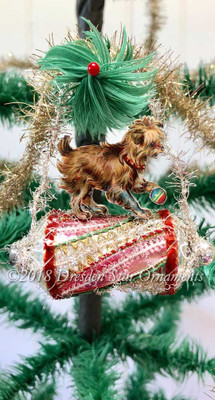 Cute Little Dog Playing on Barrel-Shaped Glass Ornament With Pink and Silver Swirls