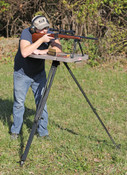 The High-Low Shooting table is a true in the field shooting table. It can be set up where no table could set before. The secret lies in the tripod design which allows it work on uneven ground, gravel, grass, hillsides, etc.. Independently adjustable legs lock securely into place via twin locks systems per leg. Stake-style steel feet that feature side stirrups for easy leveraging into the ground offering a firm hold just about anywhere nature takes you. Although not designed for hard surfaces like blacktop and concrete, they work well in a carpeted hunting blind. The High-Low's degree of adjustability is unmatched – from a low 18 inches to a whopping 55 inches off the ground – set it as high or low as suits your need. Shaped to accommodate both left and right handed shooters, the bench-style, table surface measures an ample 17 x 33 inches and will easily hold a front and back rest, ammo and other necessities. Transport is a cinch with a molded in tabletop handle and convenient tripod shoulder strap for carrying over longer distances. Made with USA and global parts.