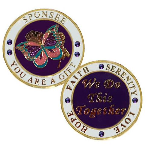 "On the front, ""Sponsee You Are A Gift"", with glitter butterfly in gold, purple, blue, pink.   On the back it reads ""Faith Serenity Hope Love"", ""We Do This Together"".   Made with gemstones."