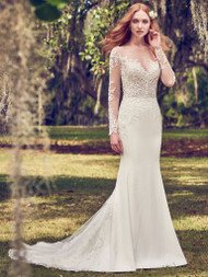 Maggie Sottero Toccara.  This Yolivia Crepe fit-and-flare features an illusion nude bodice, illusion portrait neckline, and illusion long sleeves, all embellished in beaded lace motifs. An illusion V-back accented in lace motifs complete this sleeved wedding dress. Finished with covered buttons over zipper closure. Available in: Ivory, only.