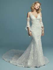 Maggie Sottero Lucienne Marie.  Embroidered lace motifs waltz over dotted tulle in this boho sheath wedding dress, completing the illusion sweetheart neckline and illusion scoop back. Featuring a breathtaking illusion double-train (Lucienne Marie, 8MS697LT) accented in lace motifs, and lined with Cypress Jersey for a luxe fit. Also available with chapel length train (Lucienne, 8MS697). Finished with covered buttons over zipper closure. Detachable illusion poet sleeves accented in lace motifs sold separately. Available in: All Ivory, Ivory over Pearl, shown.