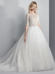 Sottero and Midgley Allen.  This show-stopping ballgown features a sheer bodice of Swarovski crystals and beading atop a voluminous tulle skirt. Complete with half-sleeves, an elegant illusion bateau over sweetheart neckline, and sexy open back. Finished with crystal buttons over zipper closure. Ivory / Pewter Accent, shown.