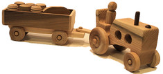 """This farm tractor is just like the one grandpa and grandma drove down on the farm. It includes a driver and six little pickle barrels and milk jugs in a detachable trailer. All you need is junior to push it along the floor. The tractor and trailer are crafted of oak or walnut and maple. They are 15"""" long x 4"""" high x 3"""" wide."""