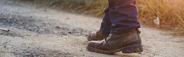 Man standing on dirt road wearing old boots