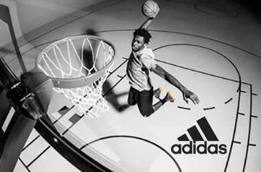 Man dunking a basketball in a greyscale picture