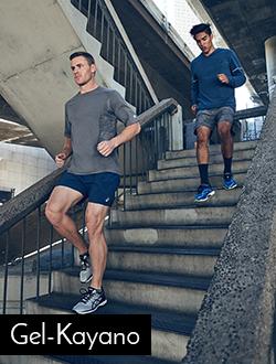 Two men running down stairs wearing Asics