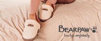 Woman sitting on a bed wearing Bearpaw