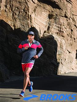Man running near mountains wearing Brooks