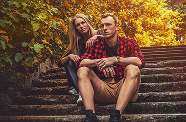 Couple sitting on stone stairs outside in Autumn wearing casual attire