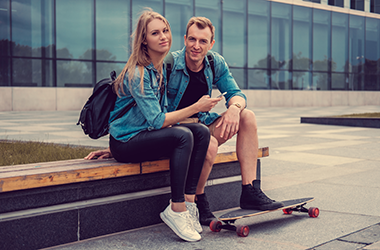 Man and Woman sitting on a bench with a skateboard under their feet