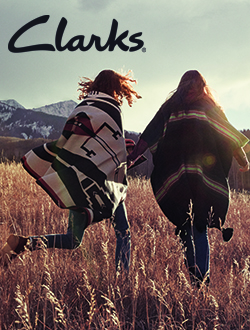 Two women wearing Clarks walking in a field with mountains in the background